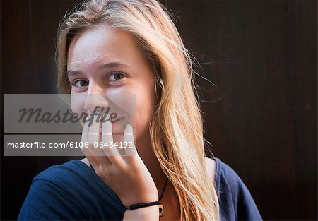 Young teenage girl smiling shyly. Stock Photo - Premium Royalty-Free, Image code: 6106-06434192