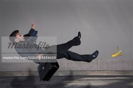Businessman slipping on a banana peel Stock Photo - Premium Royalty-Free, Image code: 6106-06434420