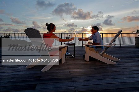 Couple drinking champagne front of the sunset Stock Photo - Premium Royalty-Free, Image code: 6106-06434739