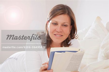 Woman lying on bed, reading a book Stock Photo - Premium Royalty-Free, Image code: 6106-06495871