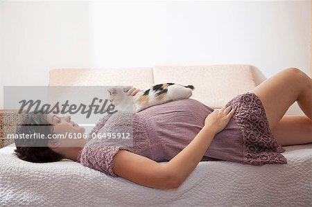 Pregnant woman in bed with her cat Stock Photo - Premium Royalty-Free, Image code: 6106-06495912
