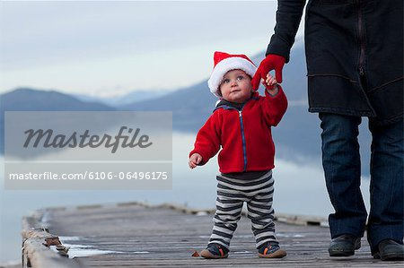 Toddler wears Santa hat and holds mothers hand Stock Photo - Premium Royalty-Free, Image code: 6106-06496175