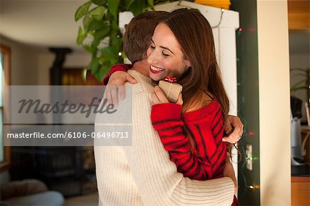Woman happily embraces partner with gift Stock Photo - Premium Royalty-Free, Image code: 6106-06496713