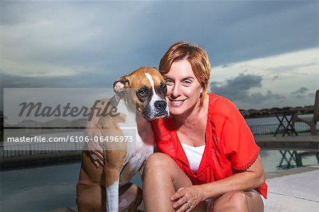 Woman with dog by the pool Stock Photo - Premium Royalty-Free, Image code: 6106-06496973