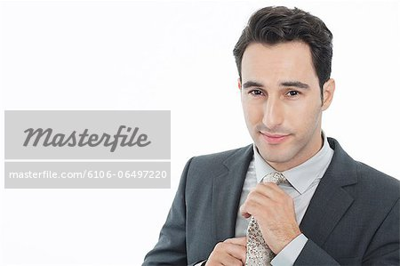 Businessman adjusting necktie Stock Photo - Premium Royalty-Free, Image code: 6106-06497220