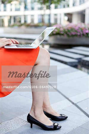 Businesswoman with modern laptop Stock Photo - Premium Royalty-Free, Image code: 6106-06497328