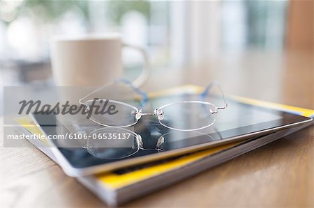 glasses, tablet PC, magazine in coffee shop Stock Photo - Premium Royalty-Free, Image code: 6106-06535137