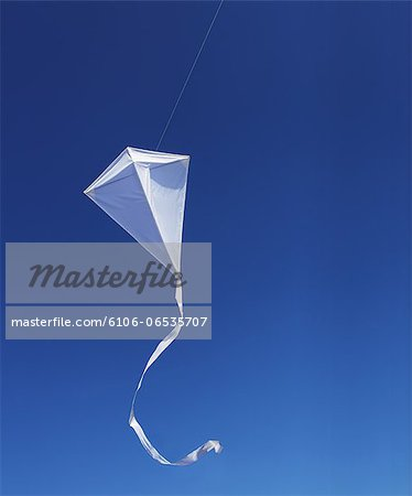 White kite against blue sky. Stock Photo - Premium Royalty-Free, Image code: 6106-06535707