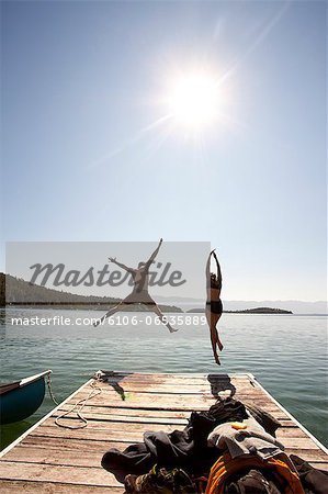 Man and woman jumping off end of dock. Stock Photo - Premium Royalty-Free, Image code: 6106-06535889