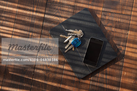 Tablet in case with keys and smartphone on top Stock Photo - Premium Royalty-Free, Image code: 6106-06830386