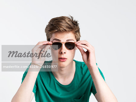 Young man wearing sunglasses Stock Photo - Premium Royalty-Free, Image code: 6106-06830977