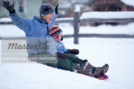 Mother sledding with toddler on winter day Stock Photo - Premium Royalty-Free, Image code: 6106-06831180