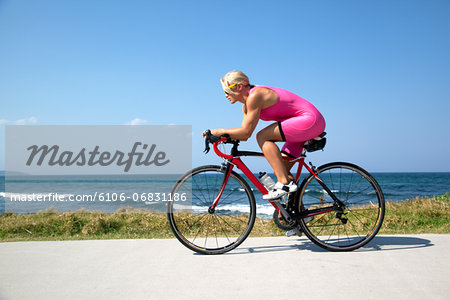 Professional Cyclist riding along Australian Beach Stock Photo - Premium Royalty-Free, Image code: 6106-06831186