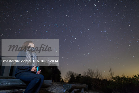 A woman sitting on a bench looking up at stars Stock Photo - Premium Royalty-Free, Image code: 6106-06832014