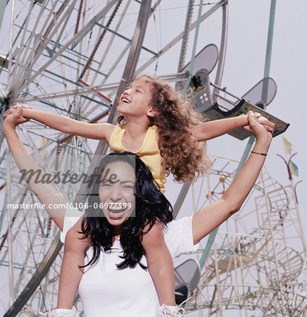 Mother carrying daughter (3-5) on shoulders at amusement park, smiling Stock Photo - Premium Royalty-Free, Image code: 6106-06977399