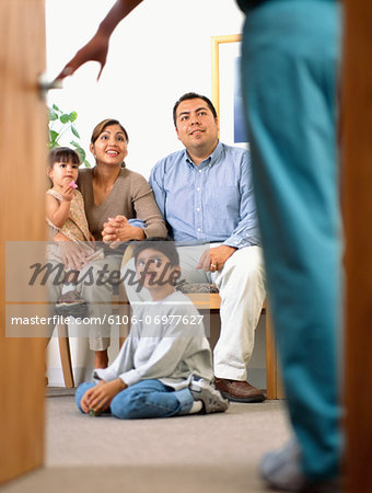 Surgeon talking to family in waiting room (focus on parents smiling) Stock Photo - Premium Royalty-Free, Image code: 6106-06977627