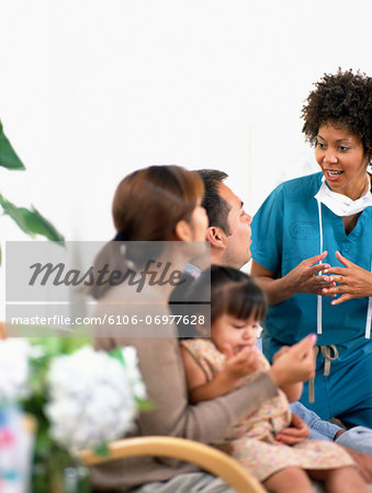 Female surgeon talking to family in waiting room (focus on surgeon) Stock Photo - Premium Royalty-Free, Image code: 6106-06977628