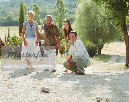 Two couples playing boule Stock Photo - Premium Royalty-Free, Image code: 6106-06978789