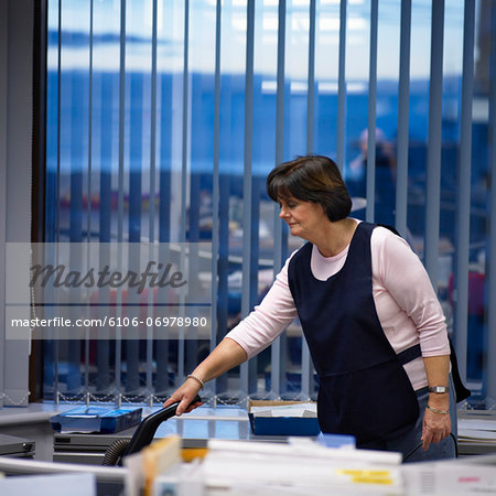 Senior woman hoovering office Stock Photo - Premium Royalty-Free, Image code: 6106-06978980