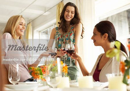 Three women raising glasses of red wine at dinner party, smiling Stock Photo - Premium Royalty-Free, Image code: 6106-06978993