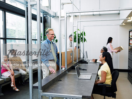 Doctor talking to receptionist, patients sitting in background Stock Photo - Premium Royalty-Free, Image code: 6106-06979940