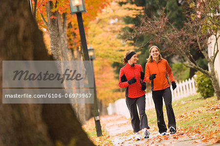 Two young women walking on sidewalk, autumn Stock Photo - Premium Royalty-Free, Image code: 6106-06979967