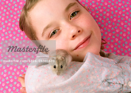 Girl (7-9) holding pet hamster, smiling, portrait, close-up Stock Photo - Premium Royalty-Free, Image code: 6106-06981689