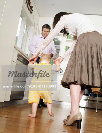 Mother helping daughter (9-12 months) walking towards father in kitchen Stock Photo - Premium Royalty-Free, Image code: 6106-06983802
