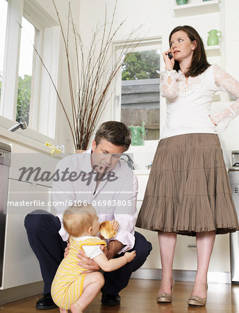 Father crouching at daughter (9-12 months) mother standing in kitchen Stock Photo - Premium Royalty-Free, Image code: 6106-06983805