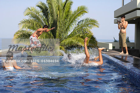 Teenagers (15-19) playing in swimming pool Stock Photo - Premium Royalty-Free, Image code: 6106-06984694