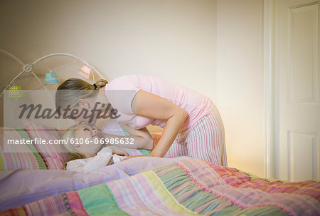 Mother kissing daughter (8-9) goodnight in bed Stock Photo - Premium Royalty-Free, Image code: 6106-06985632