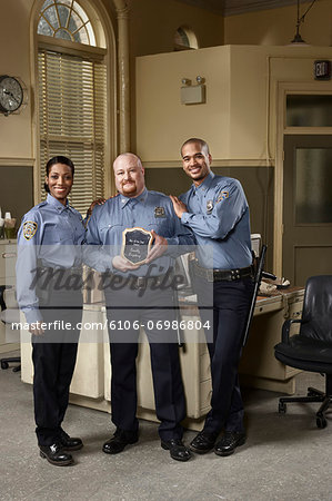 Three police officers, one holding award, portrait Stock Photo - Premium Royalty-Free, Image code: 6106-06986804