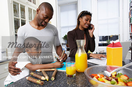 Father and son (6-7) drawing at kitchen counter, mother using mobile phone Stock Photo - Premium Royalty-Free, Image code: 6106-06988719