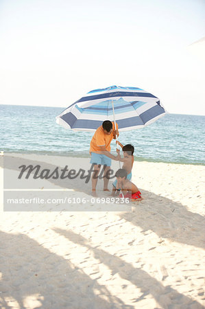 Father and two sons (6-7) setting up umbrella in sand on beach Stock Photo - Premium Royalty-Free, Image code: 6106-06989236