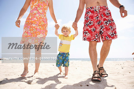 Mid adult couple walking with son (2-3) on beach, low section Stock Photo - Premium Royalty-Free, Image code: 6106-06990280