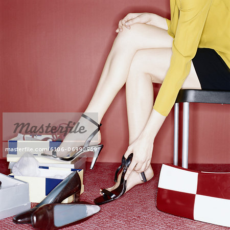 Young woman trying on shoes, low section, side view Stock Photo - Premium Royalty-Free, Image code: 6106-06990969