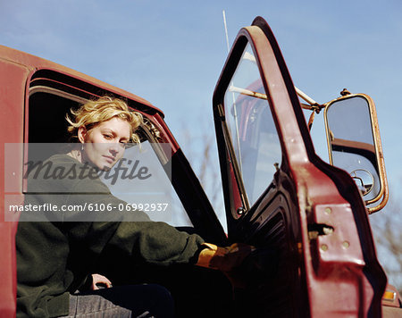 Young woman sitting in truck with the door open, portrait Stock Photo - Premium Royalty-Free, Image code: 6106-06992937