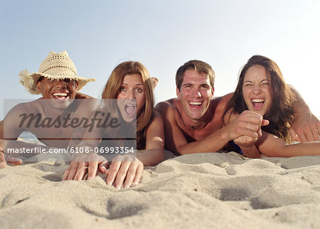 Two young couples lying on beach, portrait, close-up Stock Photo - Premium Royalty-Free, Image code: 6106-06993354