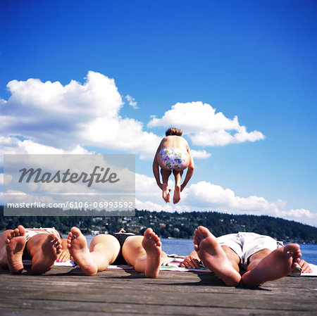 Teenagers (14-16) lying on dock, girl jumping into lake, rear view Stock Photo - Premium Royalty-Free, Image code: 6106-06993592