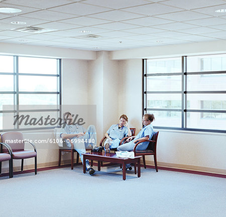 Three doctors sitting in hospital waiting room, resting Stock Photo - Premium Royalty-Free, Image code: 6106-06994480