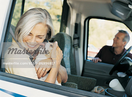 Woman Sitting in a Car and Being Licked by a Dog Stock Photo - Premium Royalty-Free, Image code: 6106-06996817
