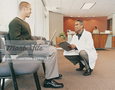 Doctor Talking to a Patient in the Reception Area of a Clinic Stock Photo - Premium Royalty-Free, Image code: 6106-06998257