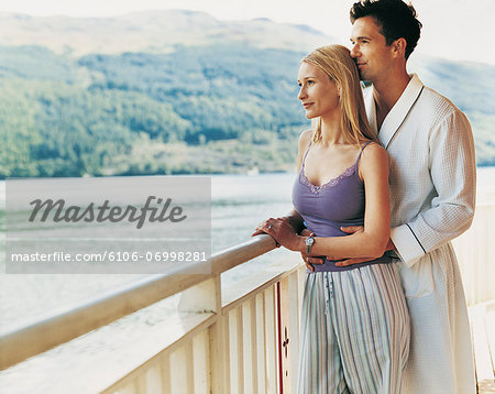 Couple Standing on a Balcony Looking at the View Together Stock Photo - Premium Royalty-Free, Image code: 6106-06998281
