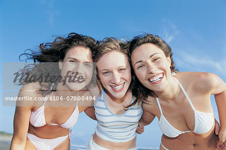 Portrait of Three, Smiling Women Standing on a Beach With their Arms Around Each Other Stock Photo - Premium Royalty-Free, Image code: 6106-07000494
