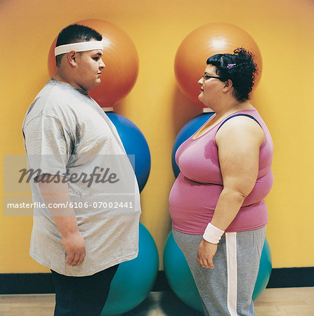 Overweight Man and Woman Standing Face to Face in a Gym Stock Photo - Premium Royalty-Free, Image code: 6106-07002441