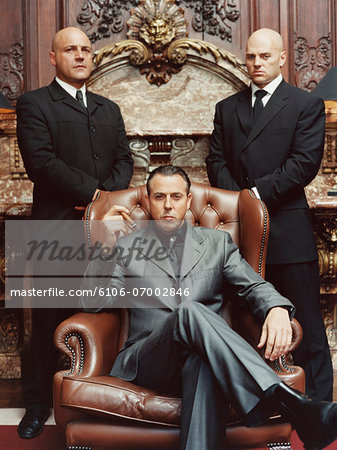 Wealthy Criminal Sitting in an Armchair Between two Bodyguards Stock Photo - Premium Royalty-Free, Image code: 6106-07002846