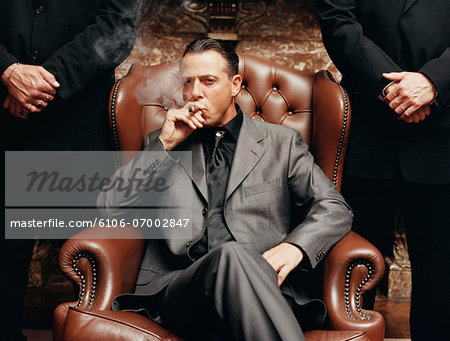 Wealthy Criminal Sitting in an Armchair Between two Bodyguards Stock Photo - Premium Royalty-Free, Image code: 6106-07002847