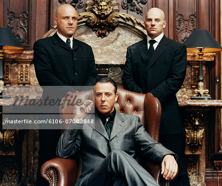 Wealthy Criminal Sitting in an Armchair Between two Bodyguards Stock Photo - Premium Royalty-Free, Image code: 6106-07002848