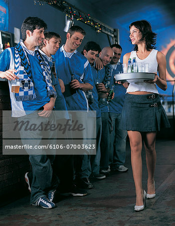 Line of Football Supporters Standing at the Bar Watching a Barmaid Walk by Stock Photo - Premium Royalty-Free, Image code: 6106-07003623