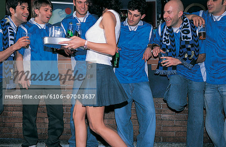 Line of Laddish Football Fans in a Bar Watching a Barmaid Carrying a Tray of Drinks Stock Photo - Premium Royalty-Free, Image code: 6106-07003637